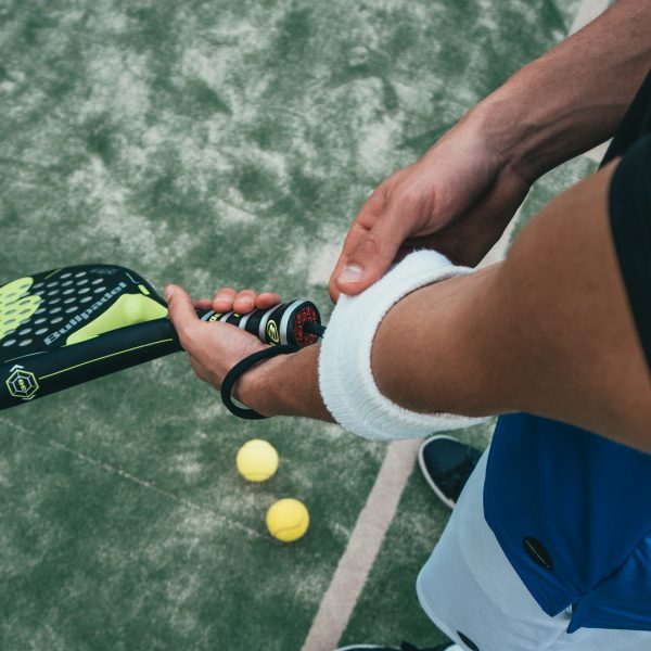 person-holding-black-and-green-tennis-racket-1103829